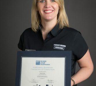 Deneale holding a certificate
